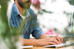 Cropped shot of male designer typing on keyboard in printing press studioの写真素材 [FYI03556998]