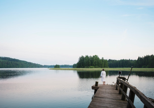 Woman wearing bathrobe with coton de tulear dog looking out from lake pier, Orivesi, Finlandの写真素材 [FYI03557099]
