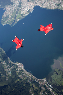 Two wingsuit skydiver pilots team training and flying close together over lake, Locarno, Tessin, Swiの写真素材 [FYI03557111]