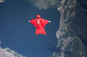 Wingsuit skydiver pilot flying over lake, Locarno, Tessin, Switzerlandの写真素材 [FYI03557113]