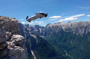 Wingsuit BASE jumper is flying from a cliff Italian Alps, Alleghe, Belluno, Italyの写真素材 [FYI03557123]