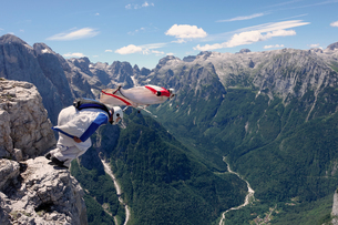 BASE jumping wingsuit pilots are jumping together from a cliff and down the valley, Italian Alps, Alの写真素材 [FYI03557124]