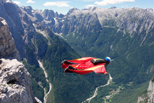 Wingsuit BASE jumper flying along cliff side and down the valley, Italian Alps, Alleghe, Belluno, Itの写真素材 [FYI03557126]