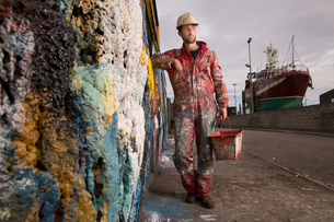 Male ship painter holding paint can leaning against paint splattered wallの写真素材 [FYI03557130]