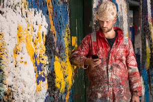 Male ship painter reading smartphone text leaning against paint splattered wallの写真素材 [FYI03557135]