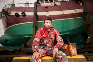 Portrait of male ship painter sitting in front of fishing boat on drydockの写真素材 [FYI03557137]