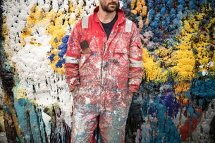 Mid section of male ship painter in front of paint splattered wall in ship painters yardの写真素材 [FYI03557146]