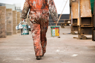 Neck down rear view of male ship painter carrying paint cans in ship painters yardの写真素材 [FYI03557152]