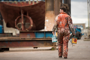 Rear view of male ship painter carrying paint cans in ship painters yardの写真素材 [FYI03557156]
