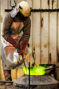 Male foundry worker working with green flamed furnace in bronze foundryの写真素材 [FYI03557175]