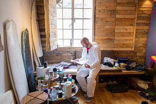 Male carpenter reading paperwork in surfboard maker's workshopの写真素材 [FYI03557192]