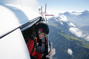 Female sky diver in helicopter checking for exit over mountain, Interlaken, Berne, Switzerlandの写真素材 [FYI03557194]