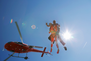 Tandem sky divers free falling with helicopter above, Interlaken, Berne, Switzerlandの写真素材 [FYI03557199]