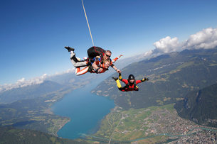 Smiling tandem sky divers holding hand with free faller, Interlaken, Berne, Switzerlandの写真素材 [FYI03557206]