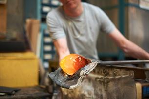 Glassblower in workshop forming molten glass on blowpipeの写真素材 [FYI03557268]