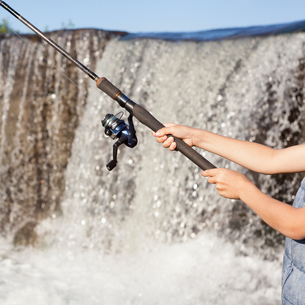 Cropped view of fisherman's fishing rod by waterfallの写真素材 [FYI03557296]