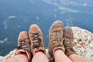 Cropped view of hikers feet wearing hiking books on rocks, Austriaの写真素材 [FYI03557330]