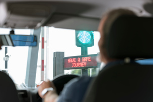 Man driving through signals at toll booth at bridge tollの写真素材 [FYI03557405]