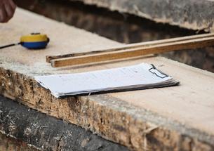 Clipboard, measuring tape on wooden plankの写真素材 [FYI03557484]
