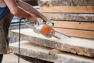 Carpenter sawing wooden plankの写真素材 [FYI03557485]