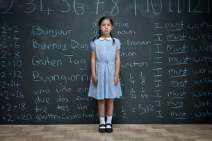 Portrait of schoolgirl standing in front of large chalkboard with schoolwork chalked on itの写真素材 [FYI03557511]