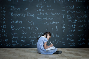 Schoolgirl sitting studying in front of large chalkboard with schoolwork chalked on itの写真素材 [FYI03557512]