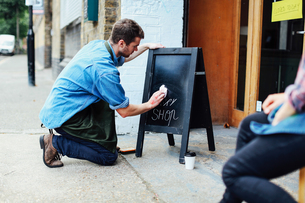 Young man kneeling on pavement and wiping blackboard outside workshopの写真素材 [FYI03557542]