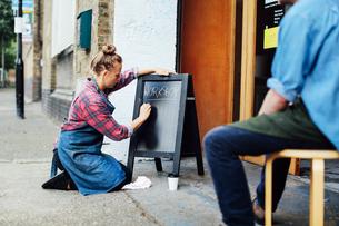 Young woman kneeling on pavement and writing on blackboard outside workshopの写真素材 [FYI03557544]