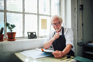 Senior craftsman holding pencil and looking at clipboard in print workshopの写真素材 [FYI03557555]