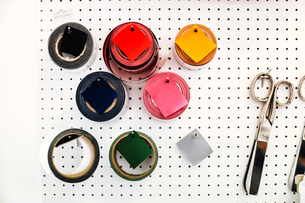 Rolls of coloured tape and scissors on wall in print workshopの写真素材 [FYI03557556]
