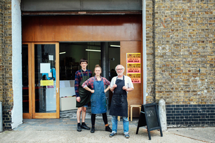 Family portrait of senior craftsman with daughter and son outside print workshopの写真素材 [FYI03557577]