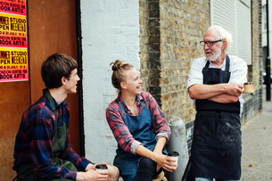 Senior craftsman chatting and laughing with young craftswoman and craftsman outside print workshopの写真素材 [FYI03557578]