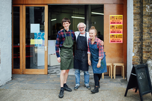 Family portrait of senior craftsman with daughter and son outside print workshopの写真素材 [FYI03557579]