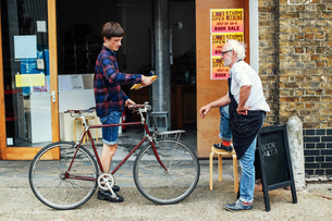 Young man with pushbike looking at post and standing with senior craftsman outside print workshopの写真素材 [FYI03557580]