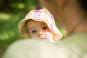 Baby girl wearing sunhat looking over mothers shoulder at cameraの写真素材 [FYI03557696]