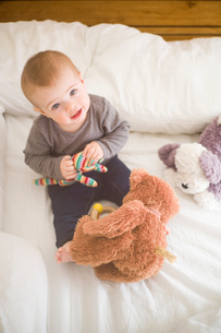 Baby girl sitting on bed holding soft toys looking up at cameraの写真素材 [FYI03557698]