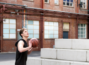 Young man playing basketball in outdoor courtの写真素材 [FYI03557732]