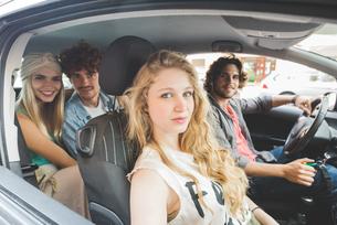 Friends sitting in carの写真素材 [FYI03557796]