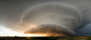 Panoramic view of a tornado-producing supercell thunderstorm spinning over ranch land at sunset nearの写真素材 [FYI03557838]