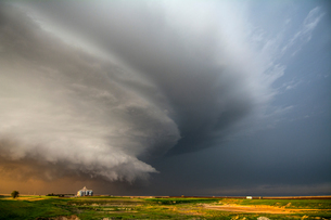 A tornado-producing supercell thunderstorm spinning over ranch land at sunset near Leoti, Kansasの写真素材 [FYI03557840]