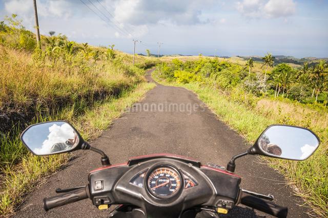 Mirror image of motorcyclist in motorcycle wing mirrors on rural road, Tanglad, Nusa Penida, Indonesの写真素材 [FYI03557859]