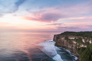 Elevated view of cliffs and sea at sunset, Uluwatu, Bali, Indonesiaの写真素材 [FYI03557888]