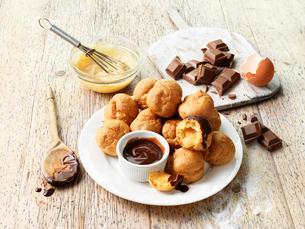 Profiteroles with hot chocolate sauce, chocolate pieces, eggの写真素材 [FYI03557978]