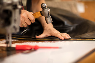 Man hammering zip on jacket in leather jacket manufacturers, close-upの写真素材 [FYI03558000]