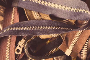 Close-up of pile of zips, in leather jacket manufacturersの写真素材 [FYI03558012]