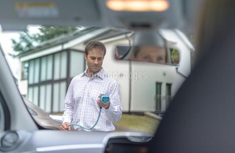 Man charging electric car, seen through car interiorの写真素材 [FYI03558039]