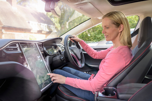 Woman using satellite navigation system in electric carの写真素材 [FYI03558043]