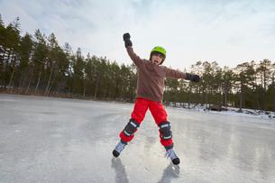 Boy balancing whilst ice skating on frozen lake, Gavle, Swedenの写真素材 [FYI03558131]
