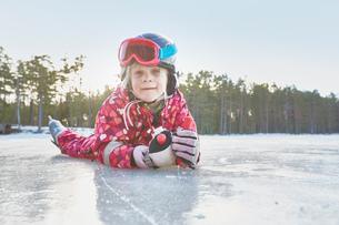 Portrait of girl lying on her front on frozen lake, Gavle, Swedenの写真素材 [FYI03558137]