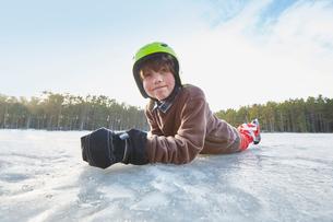 Portrait of boy lying on his front on frozen lake, Gavle, Swedenの写真素材 [FYI03558138]